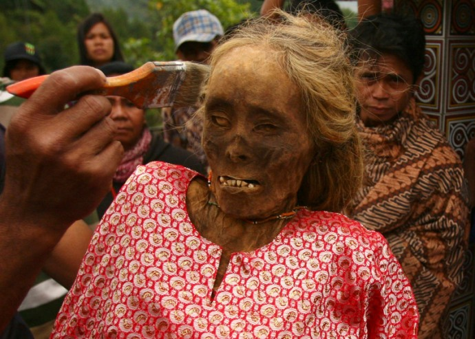 A family member cleans a mummy before giving it new clothes in a ritual in the Toraja district of Indonesia's South Sulawesi Province